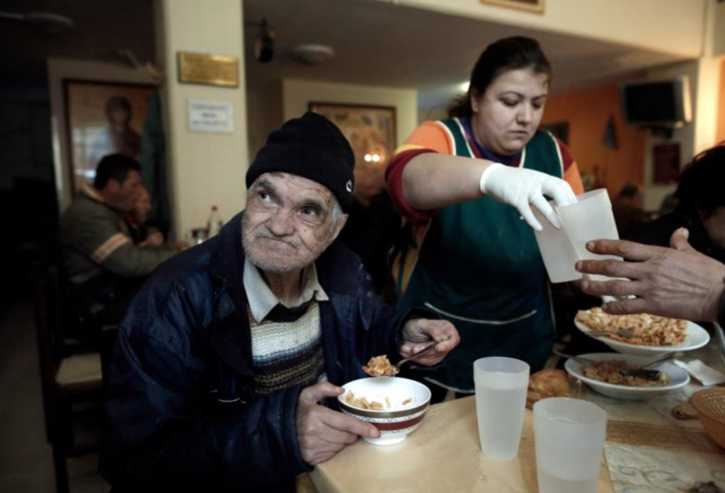"A homeless man eats his meal in 2015 at a soup kitchen run by the Archdiocese of Athens in Greece. Europe's top Catholic charitable agency has published a ""road map for social justice and equality,"" urging all church members to defend the poor and marginalized. (CNS photo/Yannis Kolesidis, EPA)"