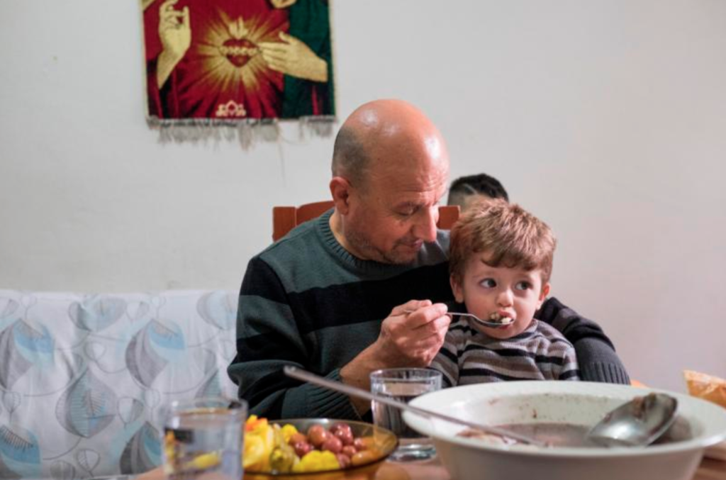 Iraqi refugee Sami Dankha, 51, feeds his son Alin, 1, at his home in Istanbul, Turkey. He lives in Istanbul with his wife and five children; his brothers live in New Zealand, Australia and the Netherlands. (CNS photo/Oscar Durand)