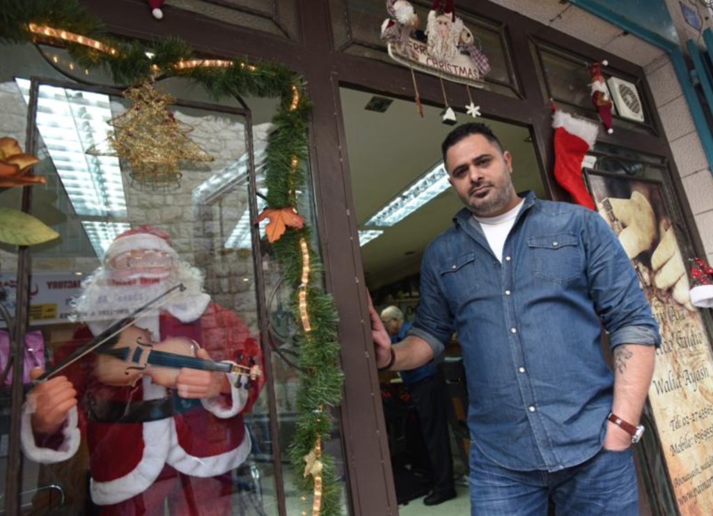 Palestinian Catholic Walid Abu Ayash, 39, tattoo artist, stands at the entrance to his barbershop/tattoo parlor Dec. 5 in Bethlehem, West Bank. (CNS photo/Debbie Hill)