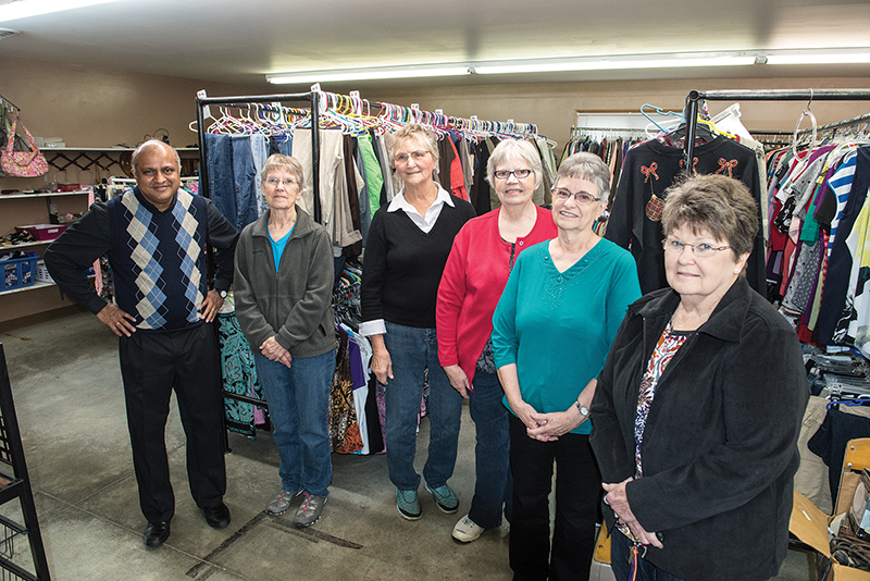 With Father Arul Carasala in the clothing section of the Seneca Mission Center are (from left) advisory committee members Rita Robke, Cleta Renyer, Laura Schmelzle, Mary Ann Augsness and Gladys Koch. They, and 60 volunteers, make the ministry a force for good in Seneca and beyond. PHOTO BY JOE BOLLIG